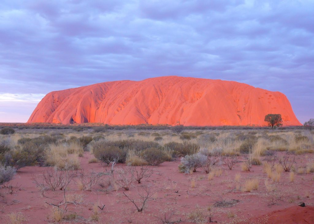 The world renowned Uluru lights up in brilliant shades of orange and red as the sun sets on another outback day.